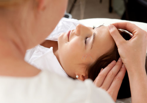 professional acupuncturist placing needle in face of patient